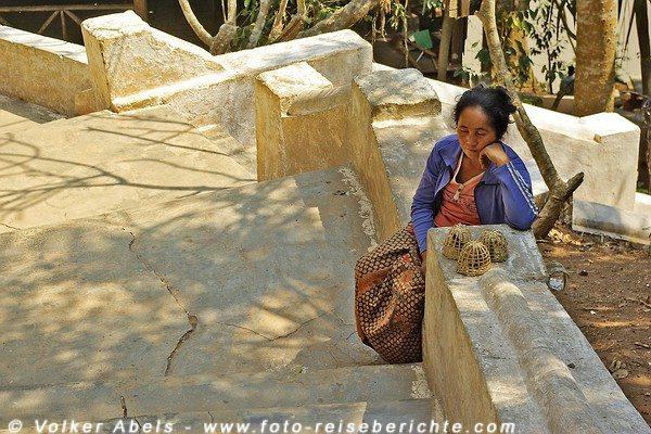 Verkäuferin, die Vögel gegen Geld frei lässt, bei den Pak Ou Höhlen bei Luang Prabang in Laos © Volker Abels