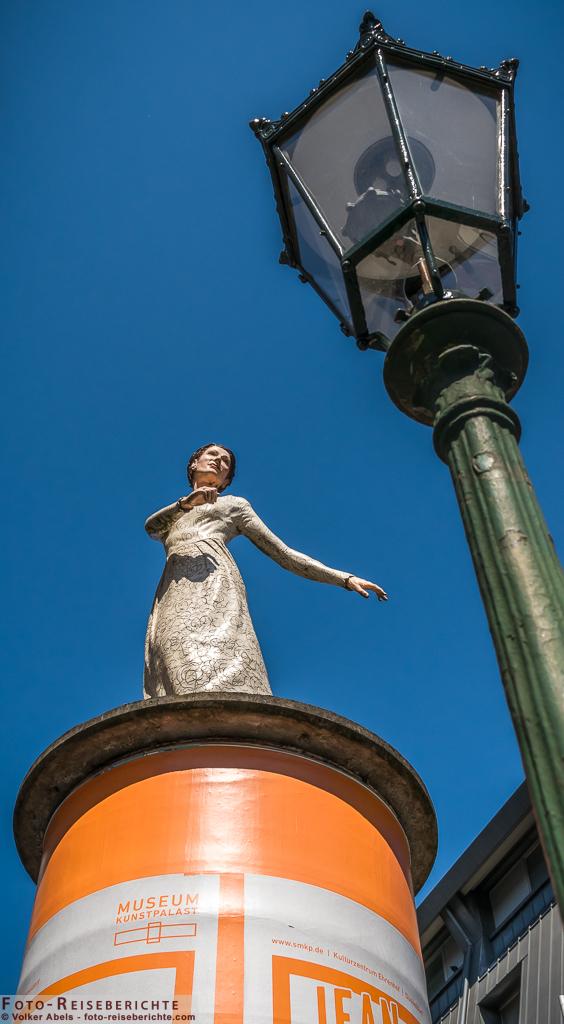 Photo of Tanzende Frauenfigur auf einer Litfaßsäule