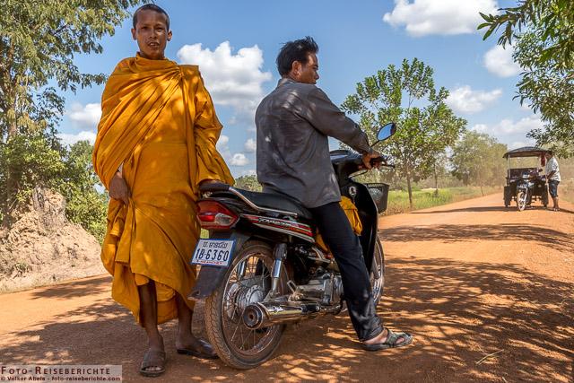Ein junger Mönch in Begleitung eines Mopedfahrers © Volker Abels - www.foto-reiseberichte.com